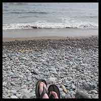 thumbnail pic of someone sitting by the ocean shore